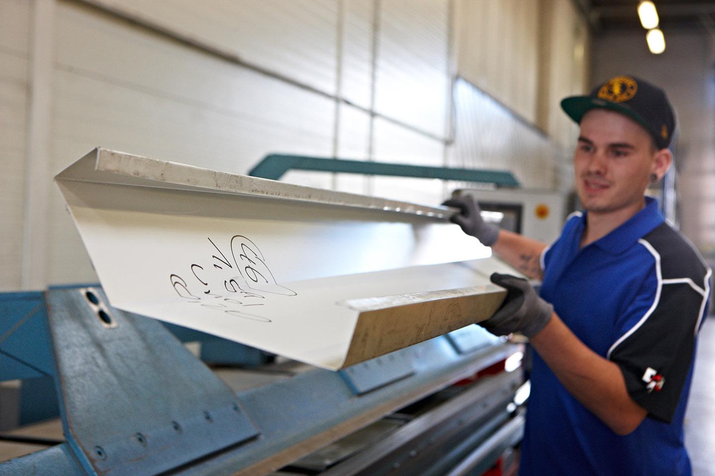 F+P Dach Kärnten - Dachtechnik - Werkstätte - Arbeiter beim bearbeiten von Blech fürs Dach - Foto: Johannes Puch